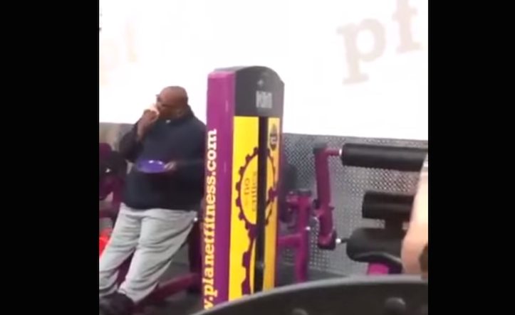 Guy eating pizza while working out