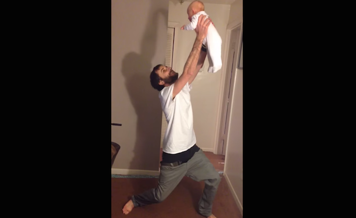 Puttings pants on holding baby