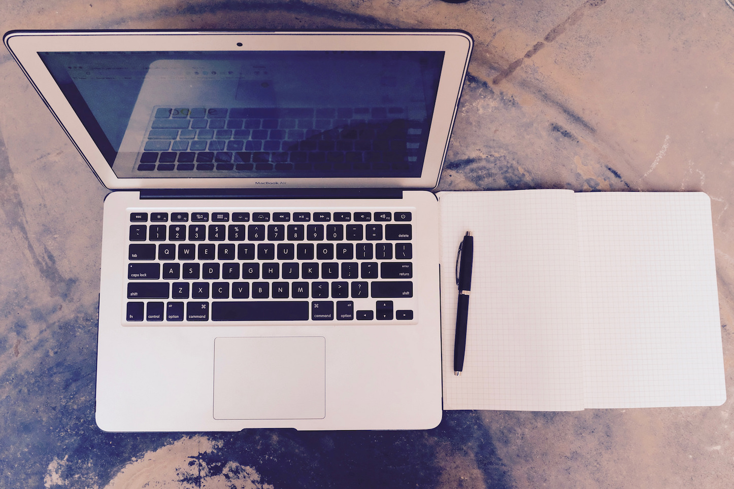 Macbook air with notebook and pen