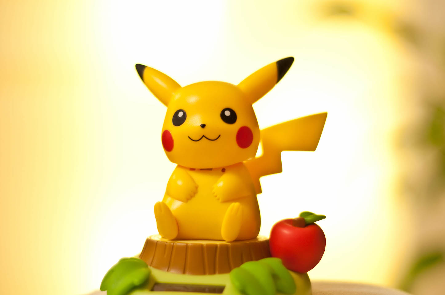 Pikachu sitting on top of a tree trunk