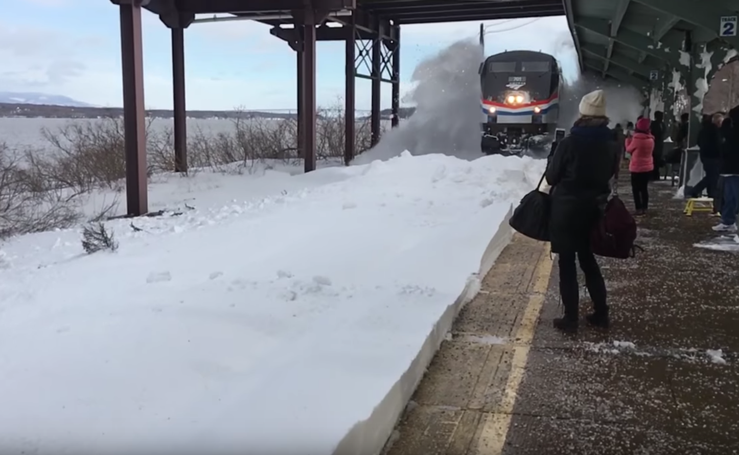 Train arriving at snow filled station