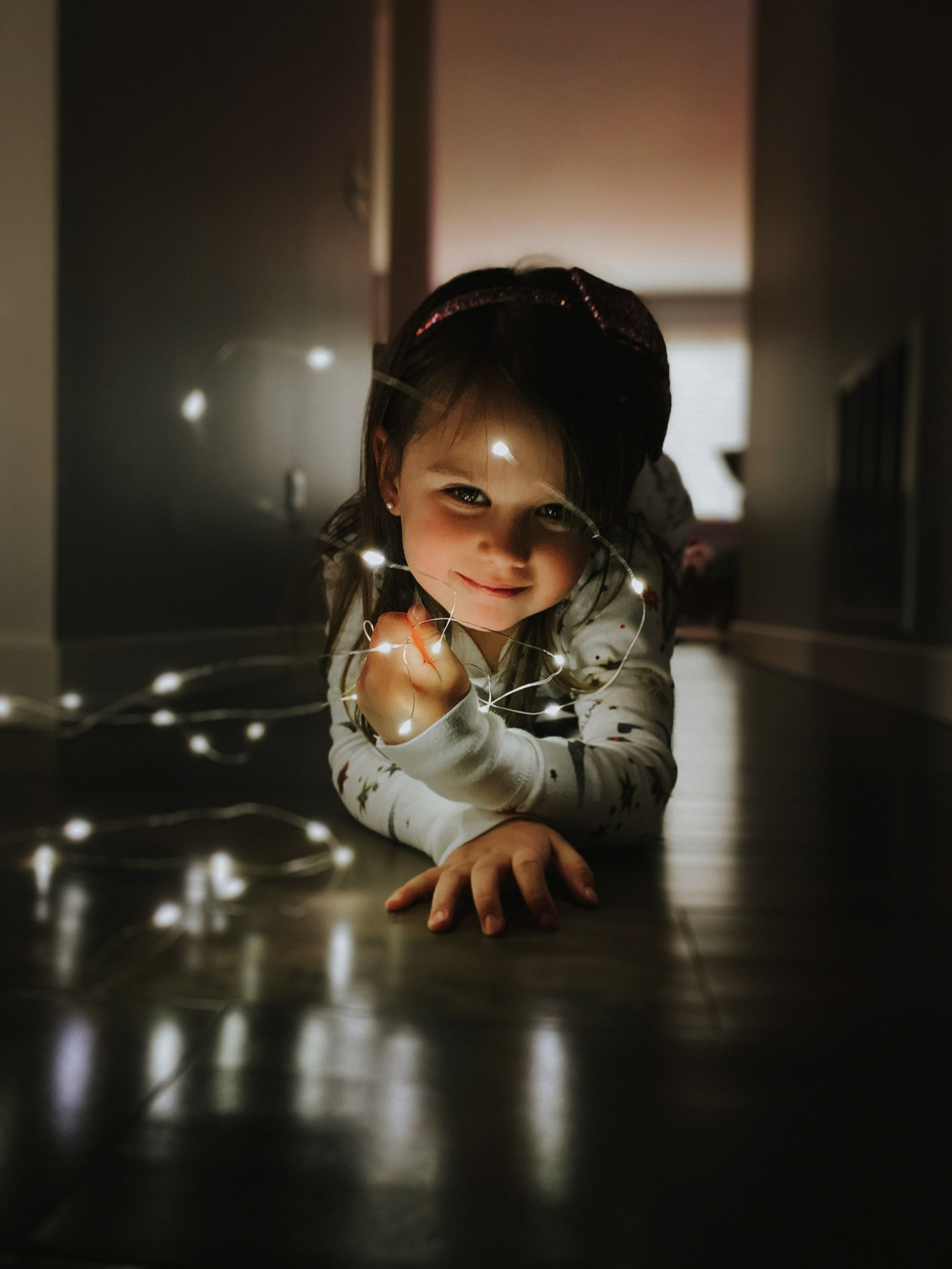 Shot on iPhone holiday Little girl with string lights 12192018