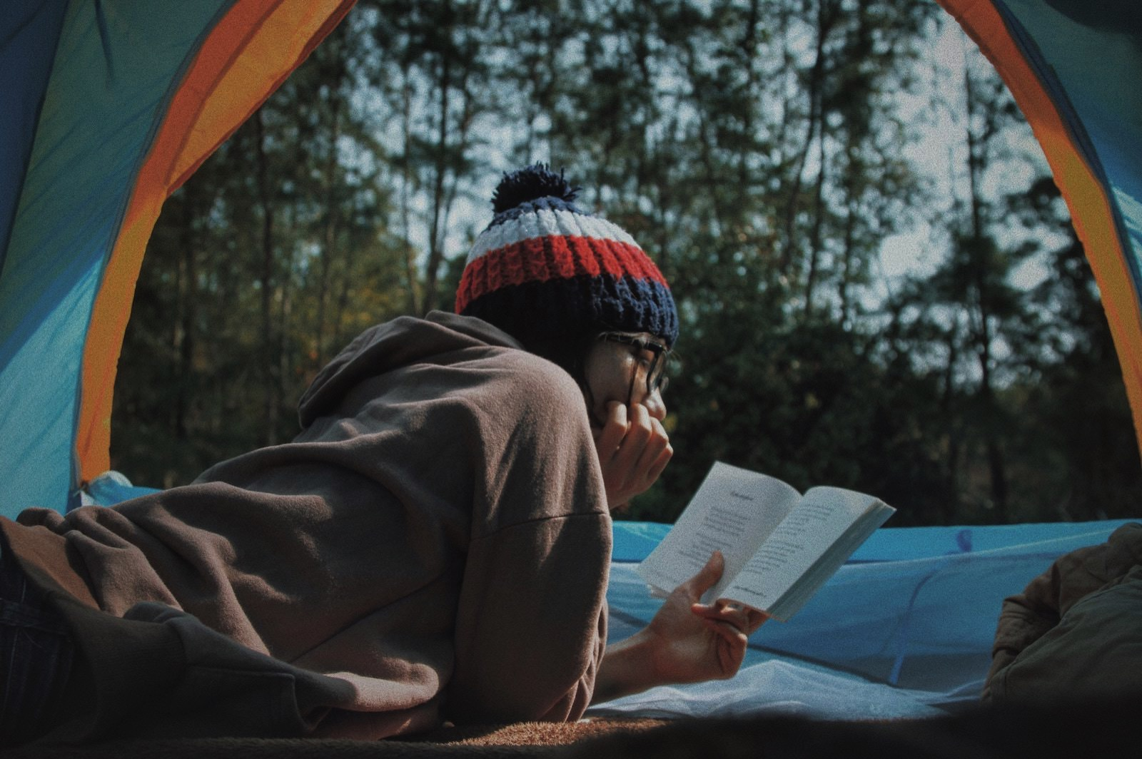 Le tan 640851 unsplash woman reading a book in tent