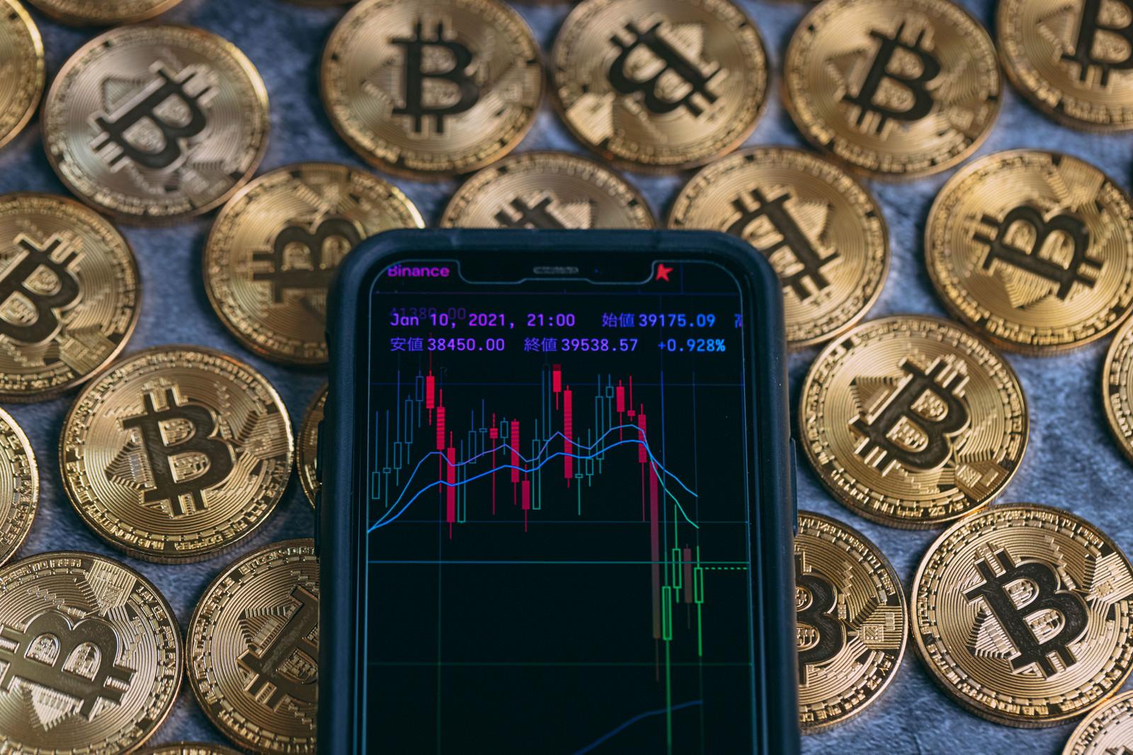 スマホのトレード画面とビットコインの写真素材